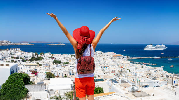 Traveler woman enjoys the view to the beautiful town of Mykonos island stock photo