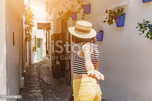 Traveler woman follow me to the famous white street with flowers in Andalusia, Spain