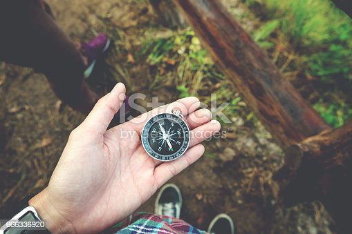 istock Traveler woman holding a compass on Mountain 666336920