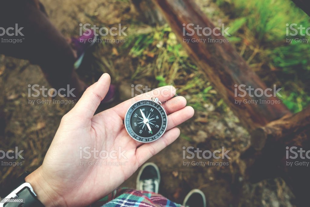 Traveler woman holding a compass on Mountain stock photo