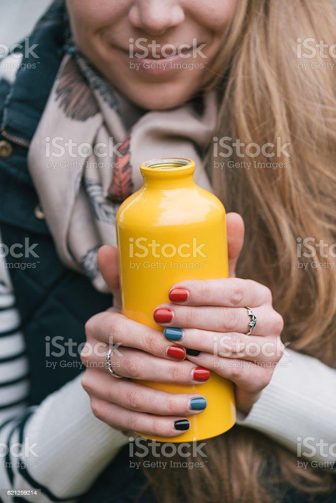 Traveler woman holding yellow thermos stock photo