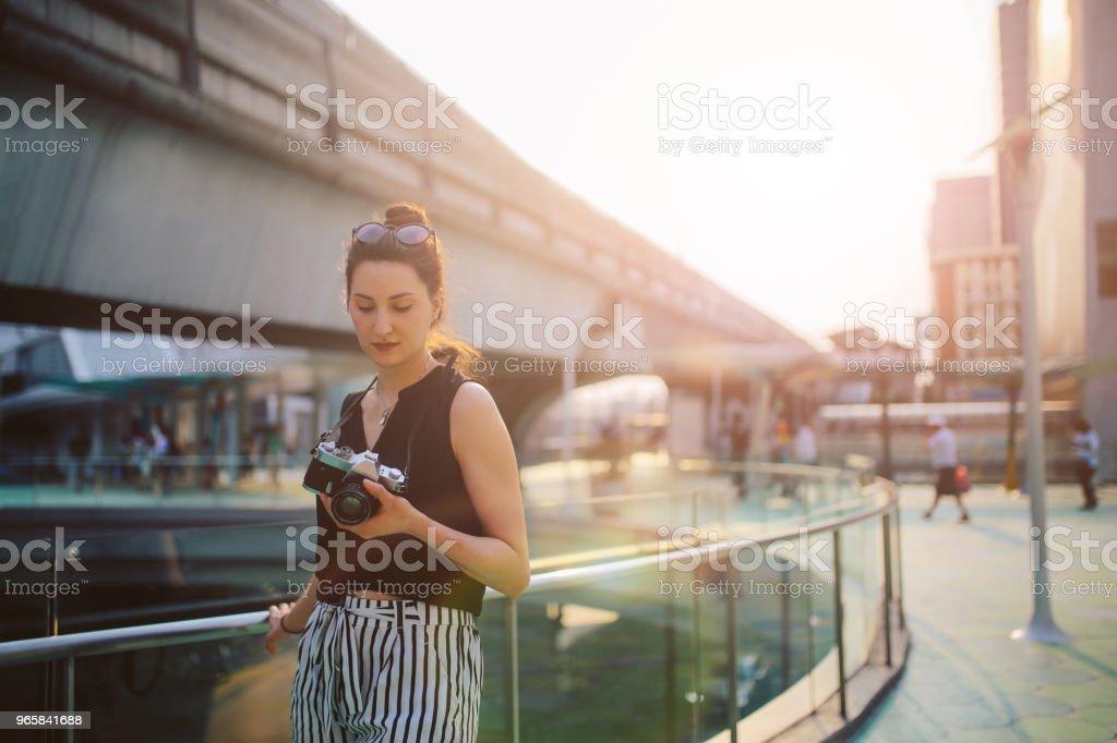 Vrouw van de reiziger in Bangkok downtown district, met een vintage filmcamera - Royalty-free Alleen volwassenen Stockfoto