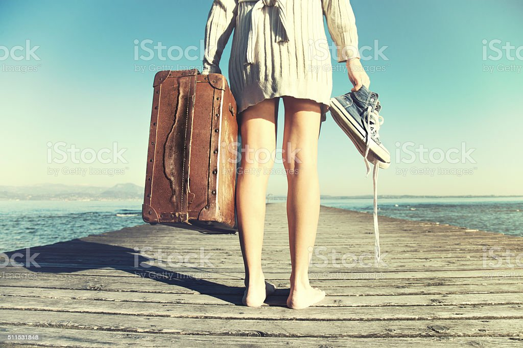 traveler woman just arrived to destination with her suitcase stock photo