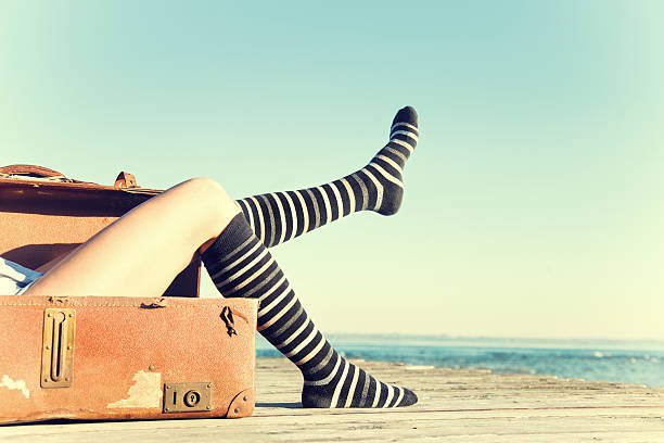 viaggiatore donna si muove le gambe seduta nella sua valigia - donna valigia solitudine foto e immagini stock