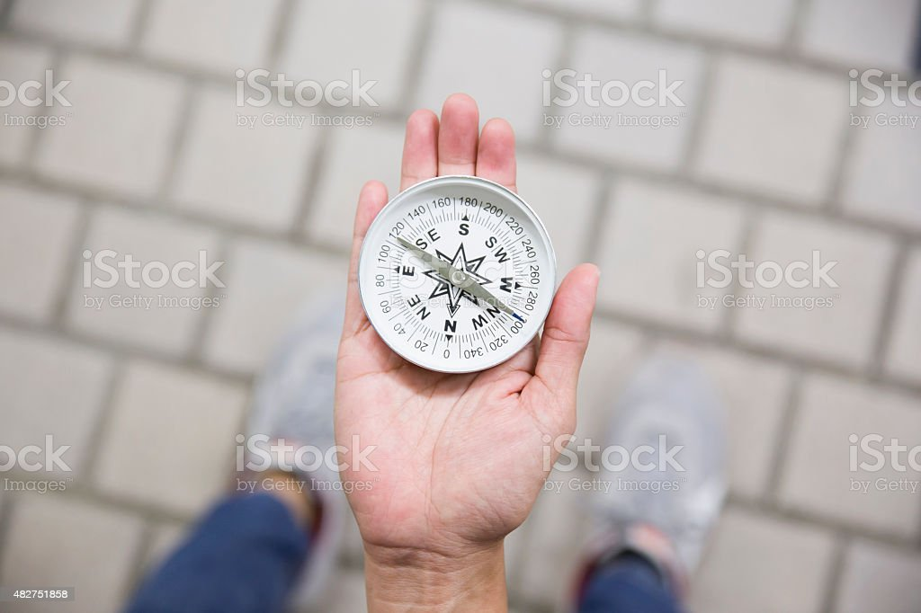 Traveler woman searching direction with a compass stock photo