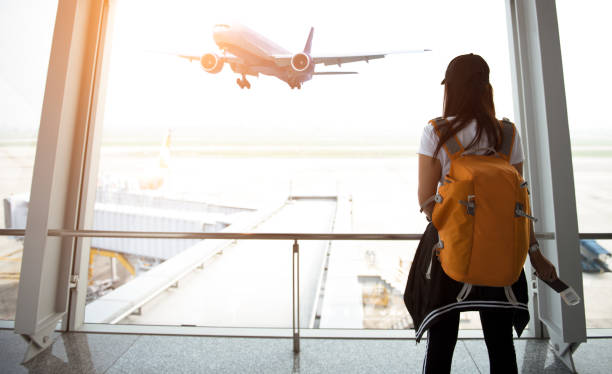 Traveler woman see the airplane at the airport window stock photo