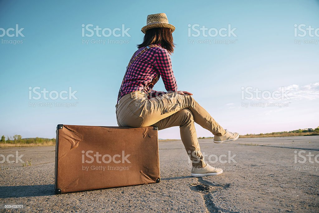 Traveler woman sits on suitcase stock photo