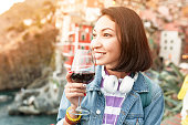 Traveler woman tasting red wine in Italy, famous Cinque Terre and Riomaggiore region. Drink and vacation concept