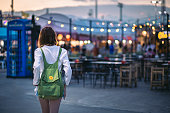 Happy young traveler asian woman with backpack sightseeing on shopping street night market with light bulb bokeh background at dusk in Bangkok, Thailand, Travel vacation city concept