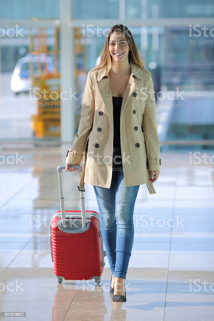 Traveler woman walking with a suitcase in an airport stock photo