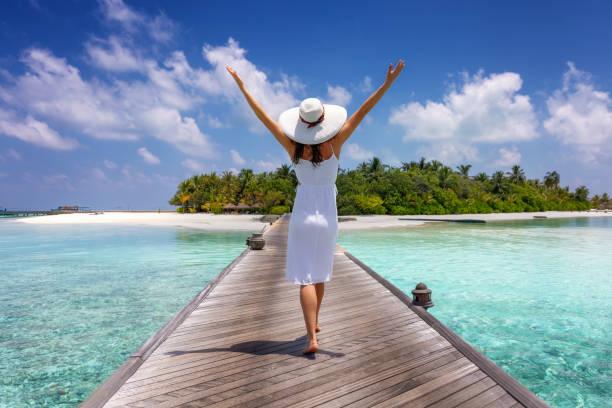 gezgin kadın tropikal bir adaya doğru ahşap bir iskeleden yürür - beyaz elbise stok fotoğraflar ve resimler