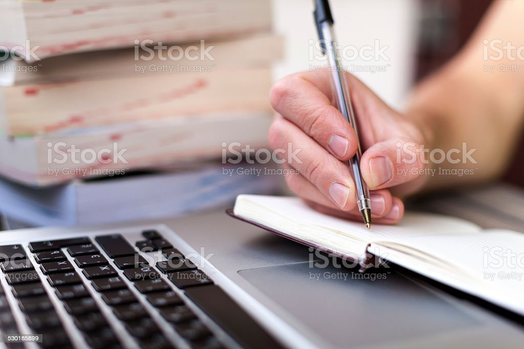 Traveler writing in a notebook stock photo