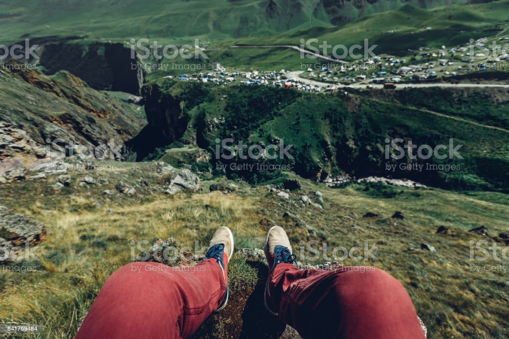 Traveler Man resting on a mountain plateau. POV view, legs close up...