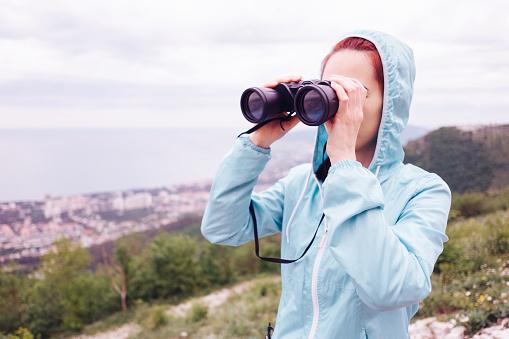 Traveler young woman looking through binoculars in summer outdoor.