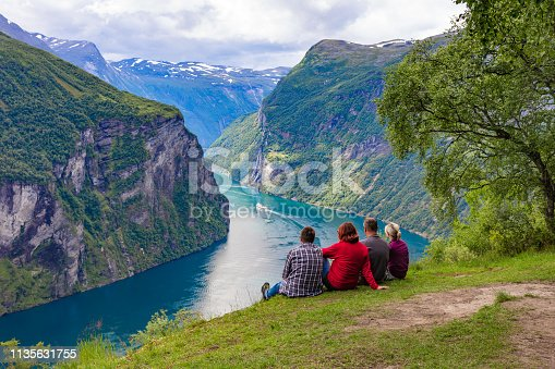Travelers  are sitting on the ground and looking at the Geirangerfjord on a cloudy summer day. The fjord is surrounded by the mountains covered with vegetation.