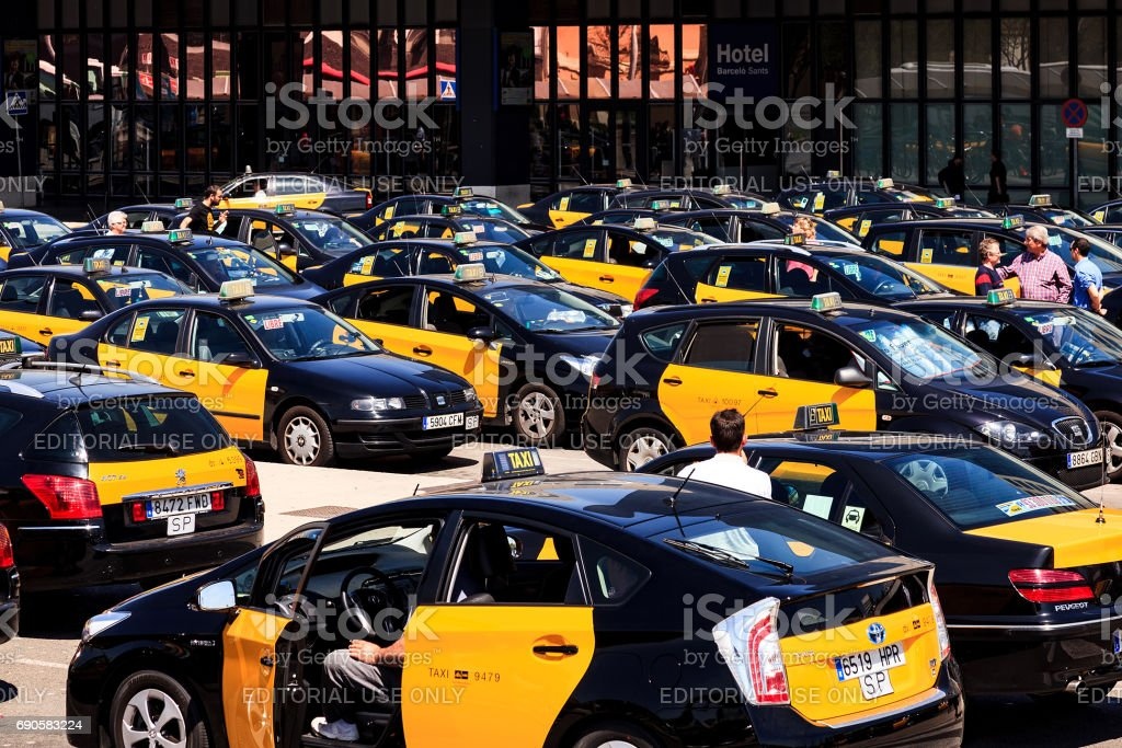 Travelers and numerous taxis waiting in front of the railway station stock photo