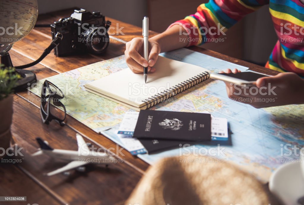 Travelers are planning a trip by searching the route on the map and searching for information on the internet. stock photo