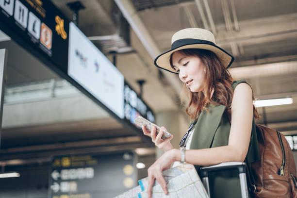 旅行者アジアの女性は、飛行機に乗る準備を空港で携帯電話でバイスタンダーフライトスケジュール - 空港 ストックフォトと画像