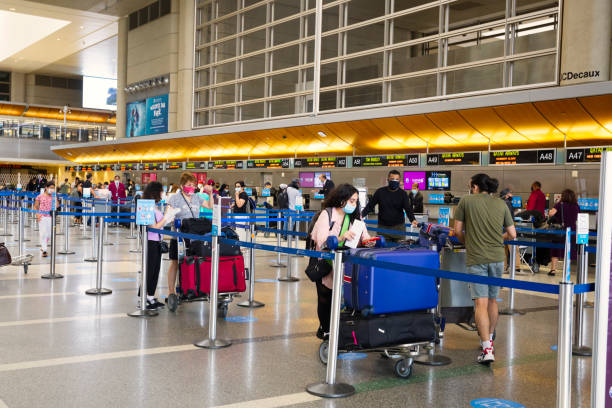 Travelers at LAX departure hall with face masks. stock photo