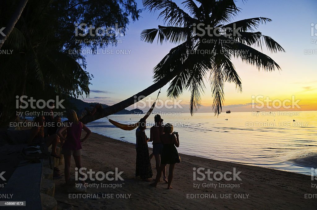 Travelers at sunset at Sairee Beach on Ko Tao royalty-free stock photo