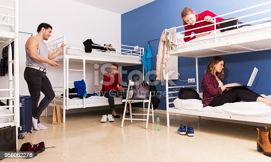 Young positive travelers communicating while resting in hostel bedroom