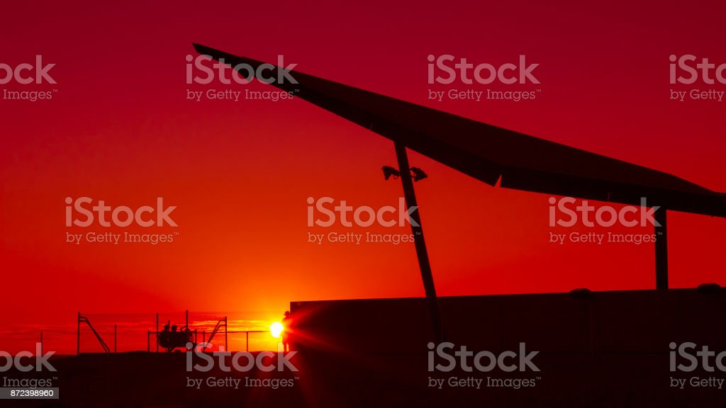 Travelers enjoying a blazing red sunset sky in the outback. Broken Hill, New South Wales, Australia. stock photo