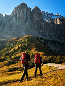 Travelers hiking in breathtaking landscape of Dolomites Mounatins in summer in Italy. Travel Lifestyle wanderlust adventure concept. Outdoor wilderness vacations.