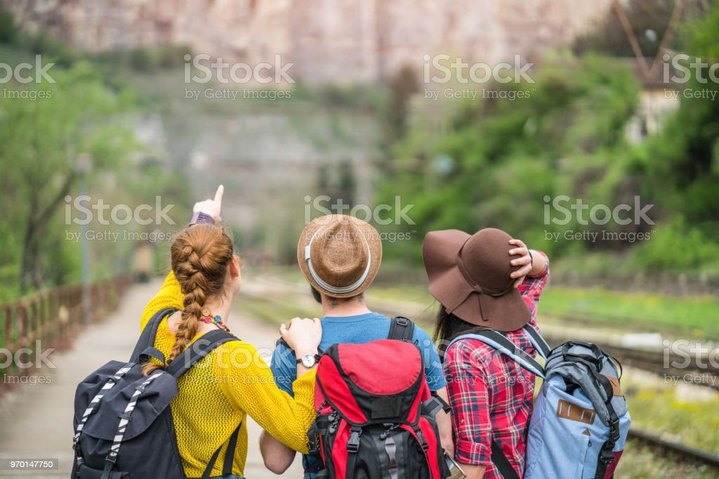 Travelers looking and pointing at the mountains while standing on the train station platform stock photo
