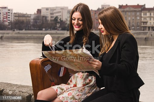 Travelers sitting near river and searching maps