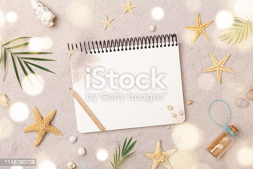 936373320 istock photo Travelers notebook with accessories on sand background top view. Planning summer holidays, trip and vacation concept. 1148760728