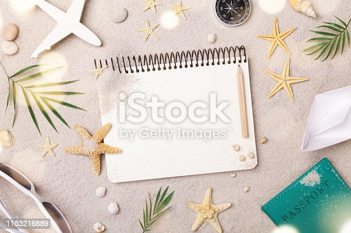istock Travelers notebook with accessories on sand background top view. Planning summer holidays, trip and vacation concept. 1153216889