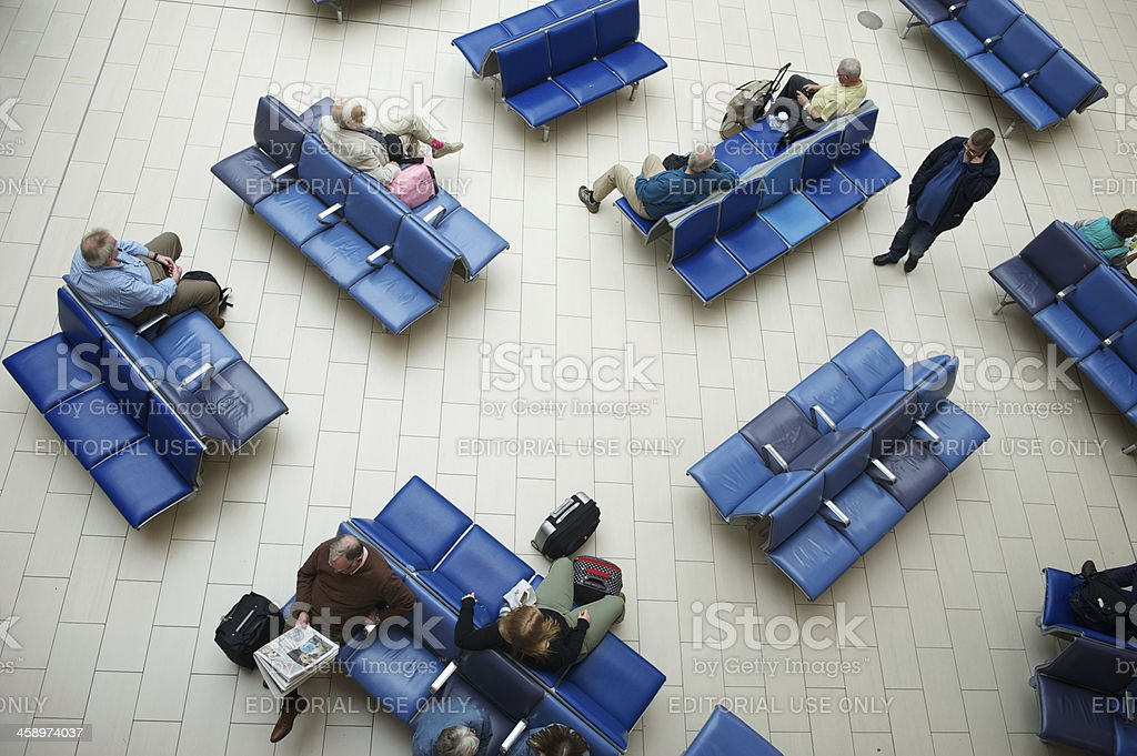Travelers Sit on Blue Seats in Airport Lounge from Above stock photo
