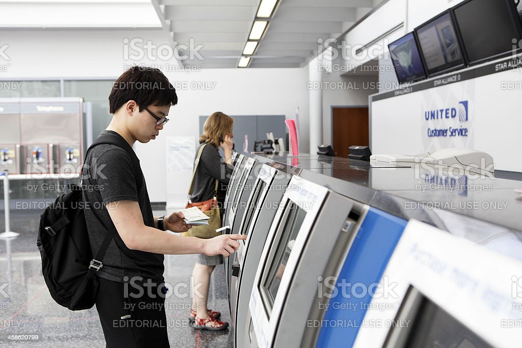 Travelers Use Automated Check-In Machines stock photo