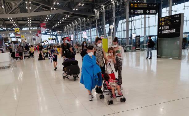 Reisende tragen Gesichtsmasken zum Schutz am Flughafen in Bangkok – Foto