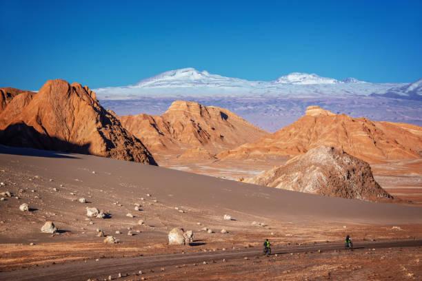 Reisende mit Fahrrädern auf einer Strecke im Tal des Mondes, Atacama-Wüste, schneebedeckten Anden-Gebirge im Hintergrund, Chile – Foto