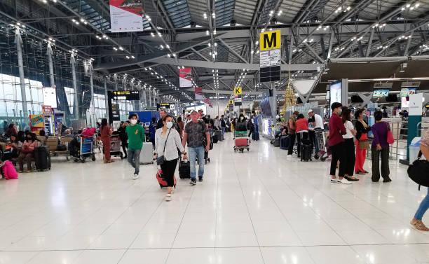 Reisende mit Gepäck am Flughafen in Bangkok tragen Masken zum Schutz gegen das Coronavirus – Foto