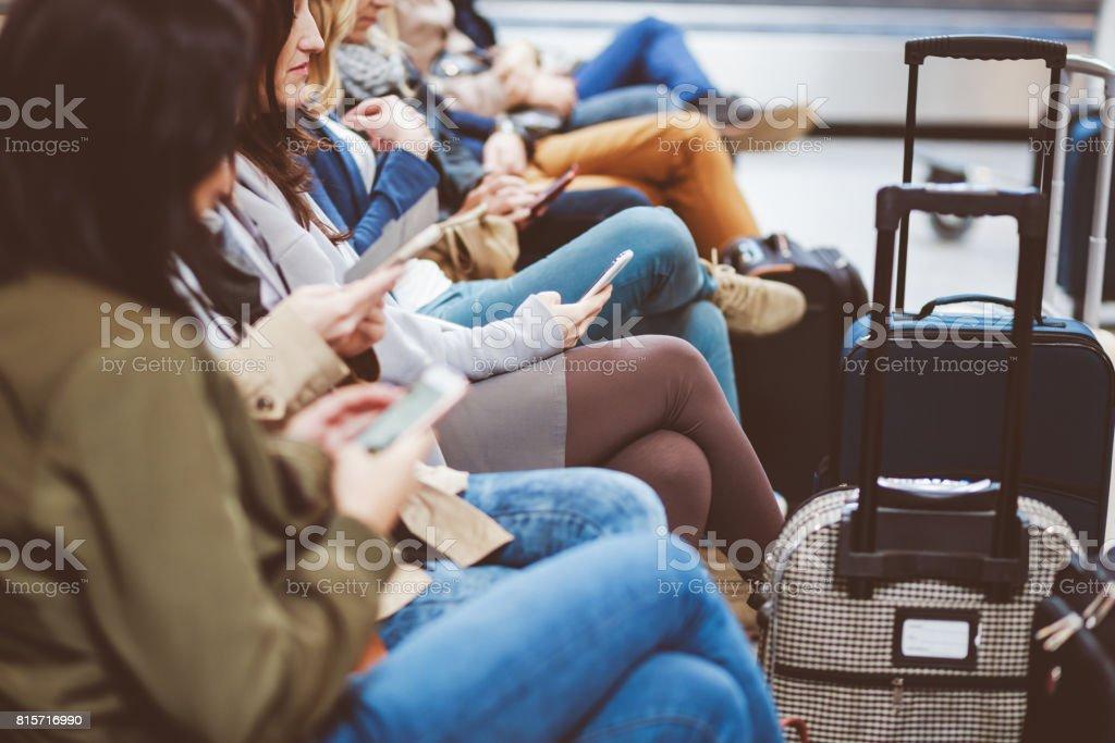 Reisende mit dem Handy am Flughafen warten. Lizenzfreies stock-foto