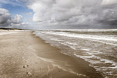 A walk along the beach in a stormy weather with a high tide in summer in Ameland, leaving footprints
