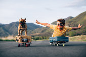 A young boy and his French Bulldog are ready to travel the world. They have put their suitcases on skateboards and are wearing flight goggles, ready to fly to new places and heights. Image taken in Utah, USA.