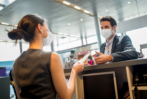 Portrait of a traveling business man doing the check-in at the airport wearing a facemask during the COVID-19 pandemic – travel concepts