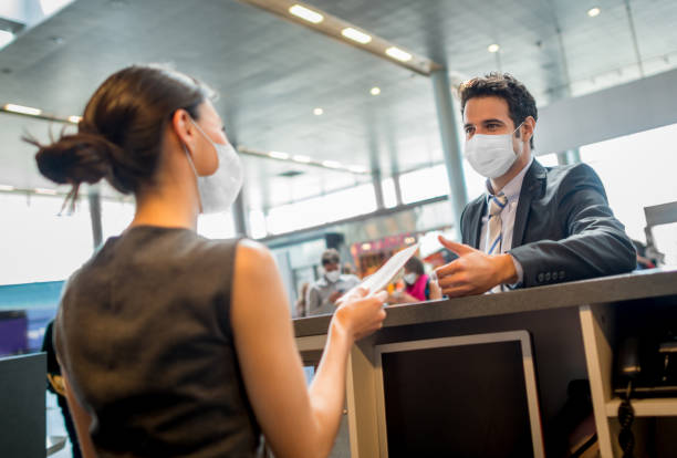 Traveling business man doing the check-in at the airport wearing a facemask stock photo
