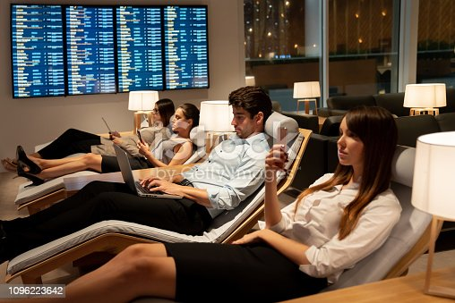 Traveling business people relaxing in a VIP lounge at the airport texting on their phone while waiting for their flight - travel concepts