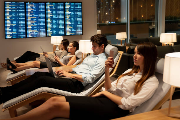 traveling business people relaxing in a vip lounge at the airport - sala d'imbarco foto e immagini stock