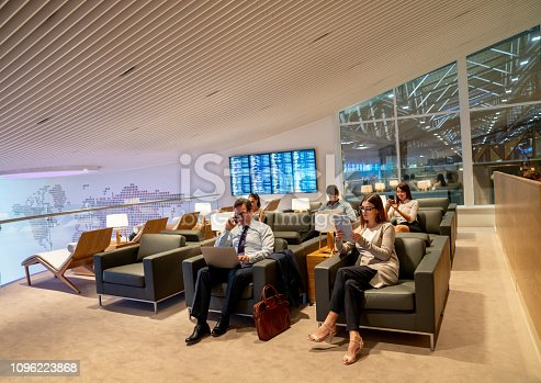 Traveling business people relaxing in a VIP lounge at the airport while waiting for their flight - travel concepts