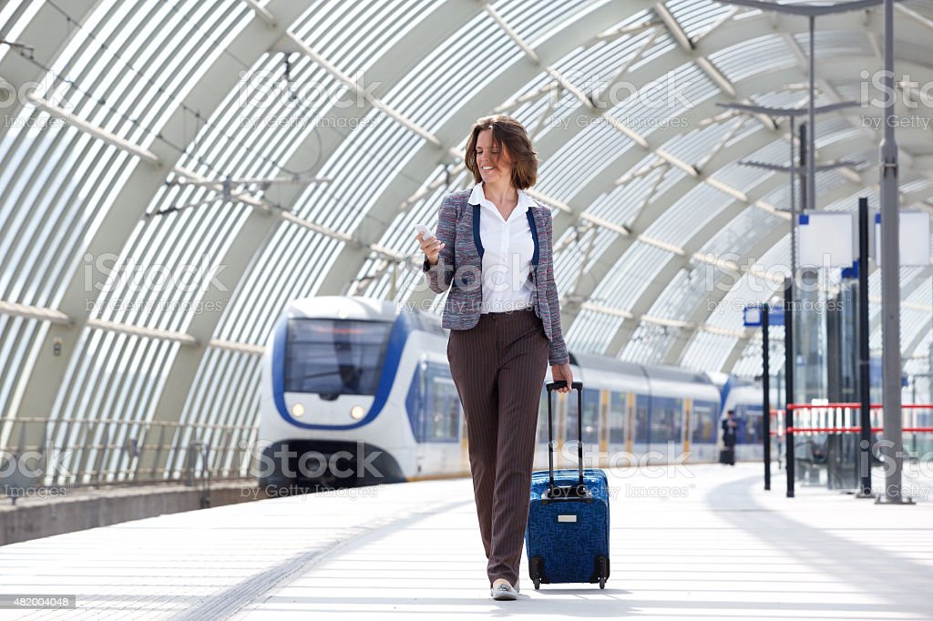 Traveling business woman walking with bag and phone stock photo