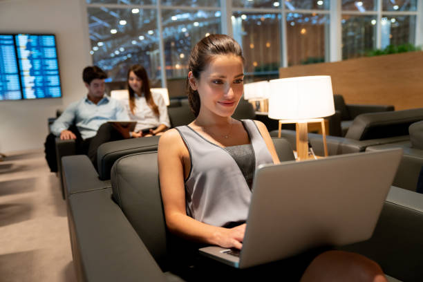 Traveling business woman working online at the airport Portrait of a traveling business woman working online at the VIP lounge at the airport - travel concepts first class stock pictures, royalty-free photos & images