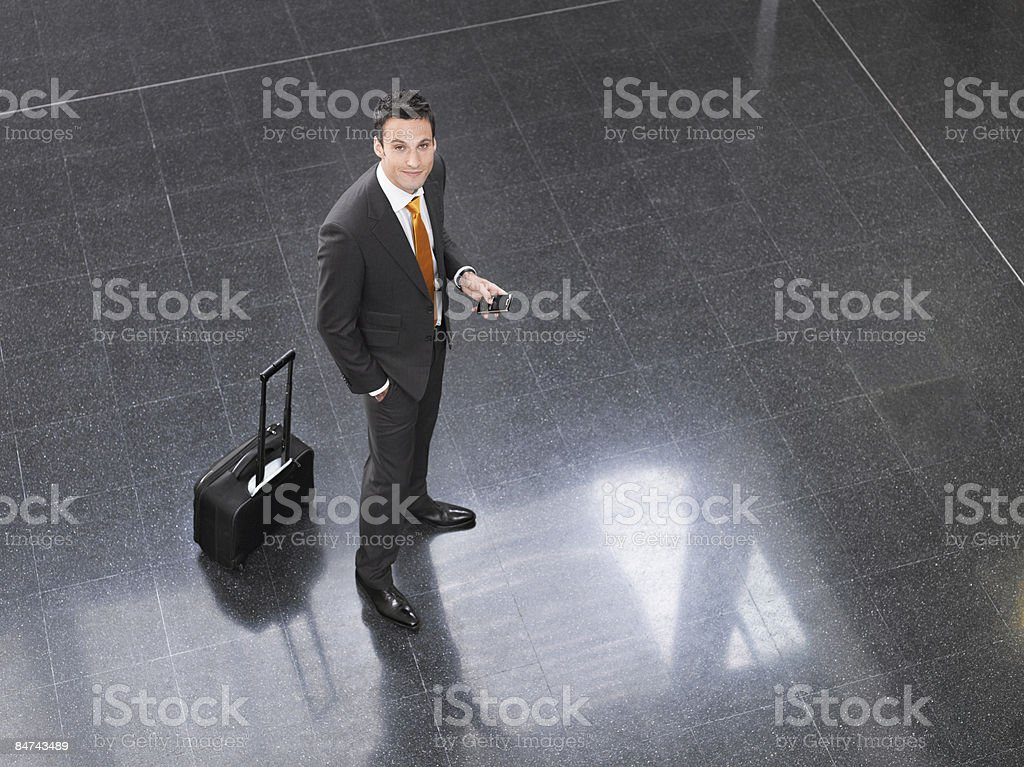 Traveling businessman standing in office lobby royalty-free stock photo
