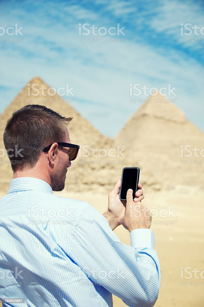 Traveling Businessman Texting on Smartphone at Great Pyramids of Egypt royalty-free stock photo