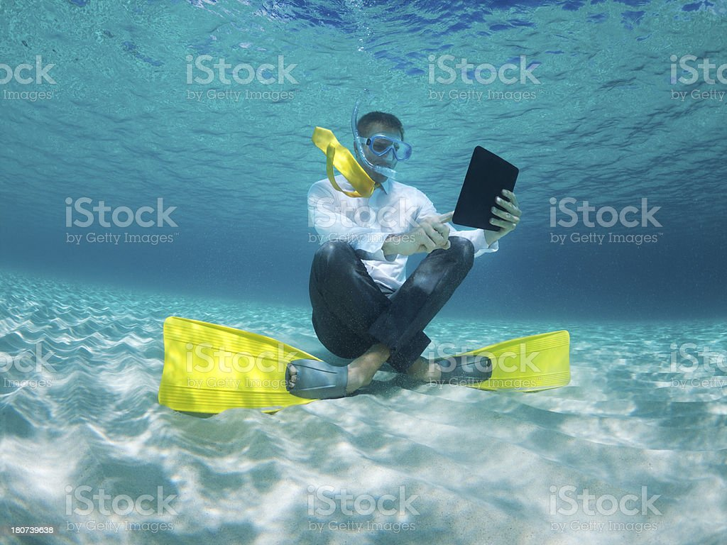 Traveling Businessman Using Digital Tablet Computer Underwater in Sea stock photo