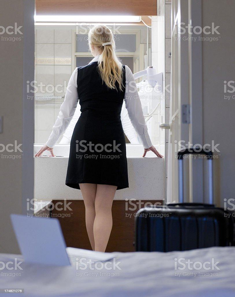 traveling businesswoman in hotel bathroom stock photo